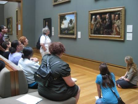 Second and third grade teachers gather around Georges de La Tour's Musician's Brawl with museum educator Kelly Williams.