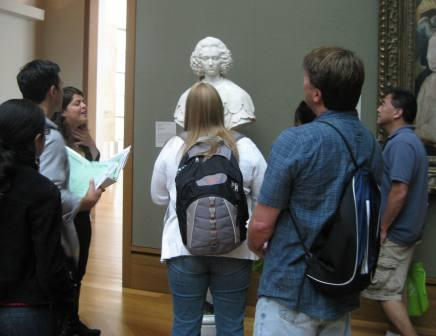 Teachers discuss a sculpture bust with museum educator Sandy Rodriguez.