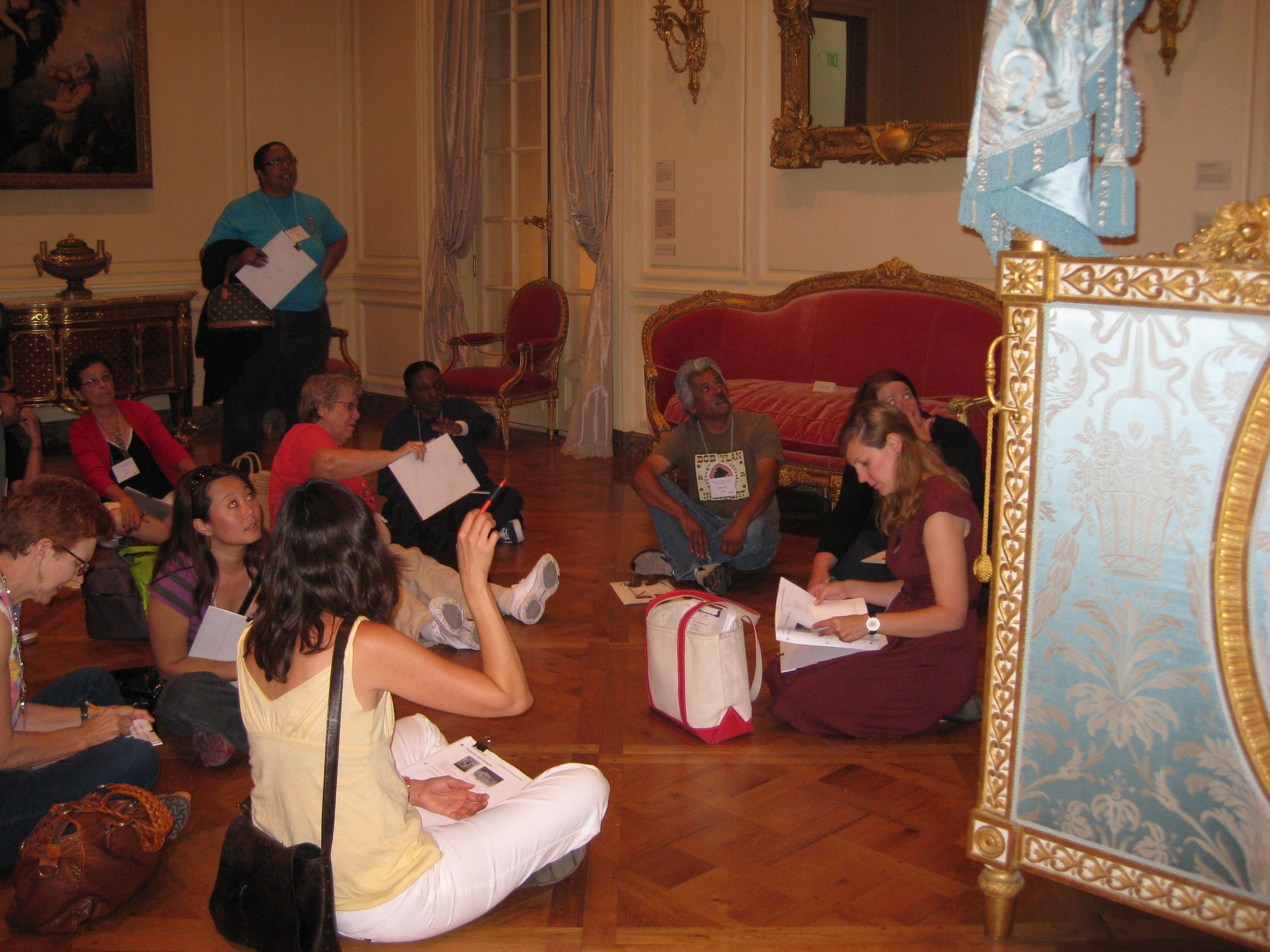 Second and third grade teachers gather around an 18th century bed.
