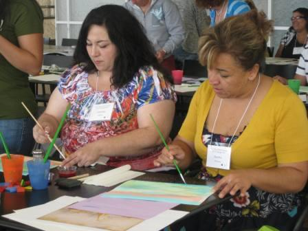 Teachers from Ellen Ochoa Learning Center paint washes after viewing a reproduction of a painting by Joseph Mallord William Turner.