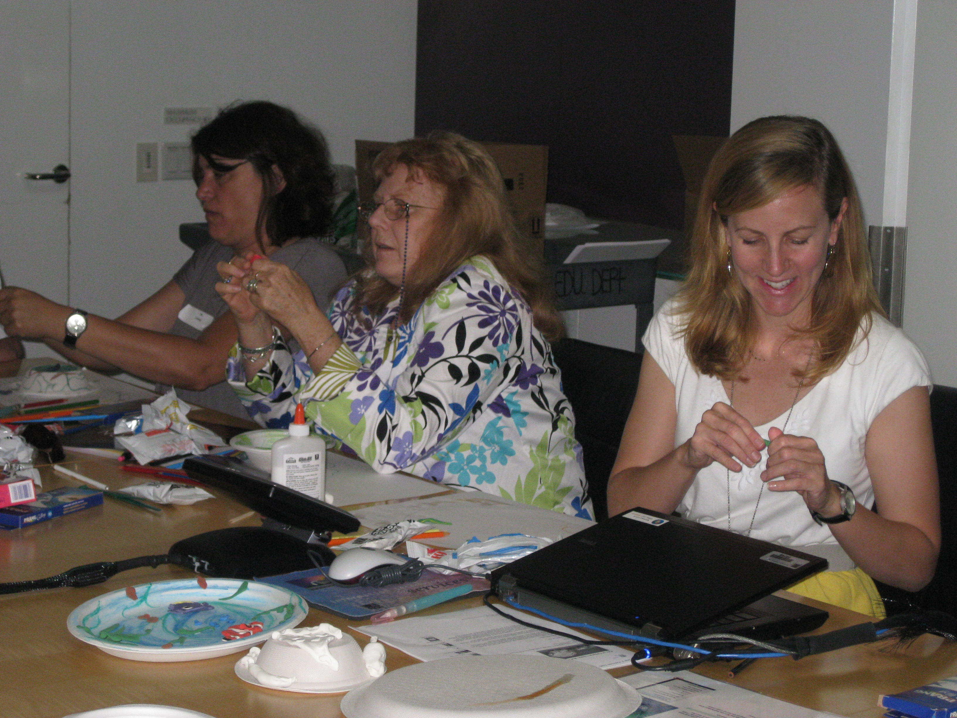 Museum educator Kelly Williams leads an activity on creating decorative plates based on a 16th-century dish and an 18th-century centerpiece depicting ingredients for a stew.