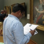 A teacher reads background information about a painting in order to help him formulate good discussion questions.