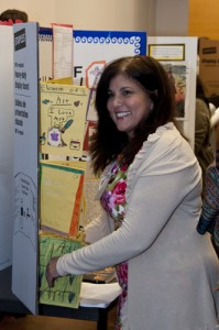 Teacher Rita Rivero stands in front of her display and the impressive portraits her students made.