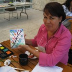 Teacher Rosa Bogarin holds up her colorful work of art.