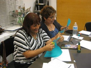 Participants cut shapes out of colored vellum for their still life collages.