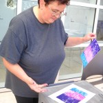Teacher Diana Bosworth views the colorful results of her print.