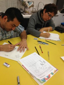 Ethel Bojorquez and Daniel Santoyo are focused on creating drawings for their manuscript pages.