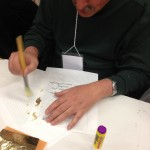 "Teacher Raymond Little brushes off excess ""gold leaf"" from his page."