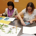 Teachers from Kennedy Elementary School arrange their objects onto light-sensitive paper.