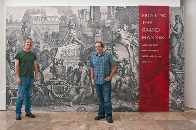 Jobe Benjamin (left) and John Kiffe (right) of GRI Digital Services in front of the entry wall to the exhibition, which features Audran's engraving of The Triumph of Alexander