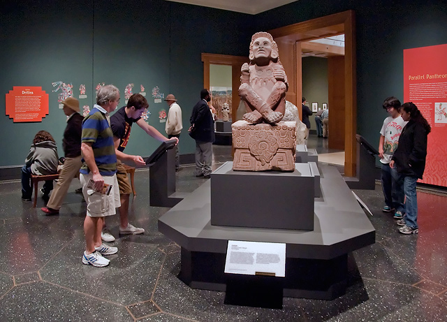 Installation view of <em>The Aztec Pantheon and the Art of Empire</em> at the Getty Villa. In the background, a wall graphic introducing deities from the Aztec pantheon. In the foreground, an Aztec sculpture of Xochipilli from 1450–51. (Museo Nacional de Antropología, Mexico City. CONACULTA-INAH-MEX © foto zabé;. Reproduction authorized by the National Institute of Anthropology and History)