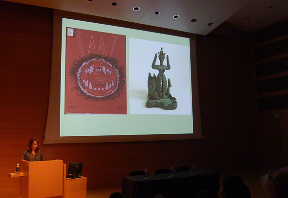 Terri Geis, research assistant at LACMA, at the podium. Images shown: Cover of VVV magazine, Issue No. 4, March 1943 (left); goddess sculpture by María Martins featured in the magazine (right)