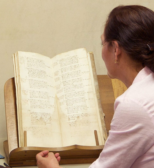 "A member of the ""Years of the Cupola"" project team consulting a manuscript from the archive"