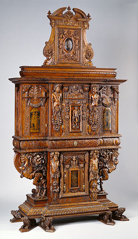 Cabinet by an unknown maker, French 1580 with minor additions from the late 1850s. Carved walnut and oak with painted panels, linen and silk lining. 10 ft. 1 1/8 in. high. Details below: drawer pull, <em>grisaille</em> painting on the right door, and a carved figure