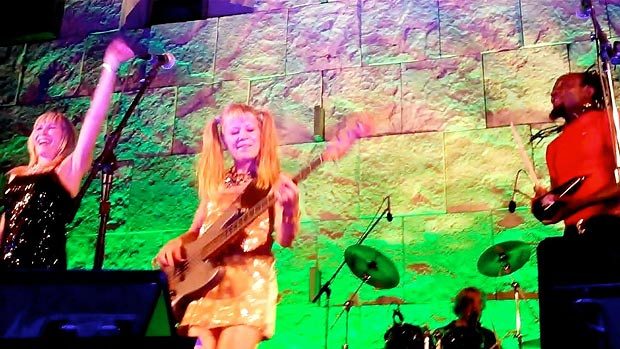 Tina (foreground) on bass in gold and pigtails, with vocalists, and Chris on drums in the background