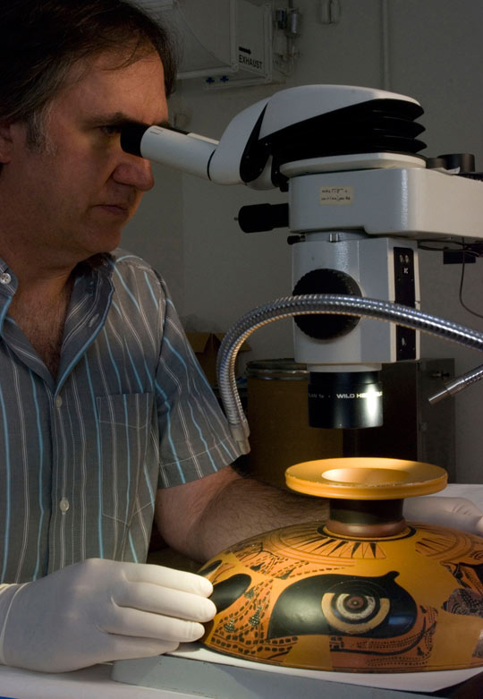 J. Paul Getty Museum Associate Conservator Jeffrey Maish examining an Attic black-figure <em>kylix</em> under a binocular stereo-microscope. Getty Conservation Institute