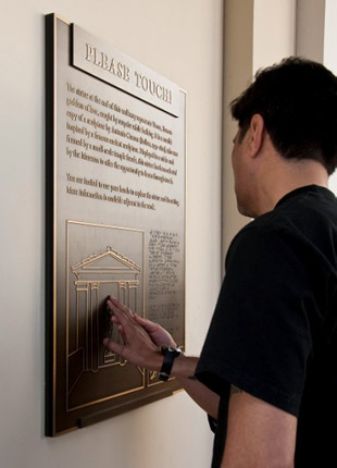 A visitor explores the Braille signage by the Touch Statue at the Getty Villa