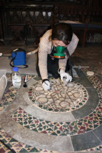Conservators consolidating the Purbeck marble tracery within one of the original remaining roundels. Courtesy of Westminster Abbey.
