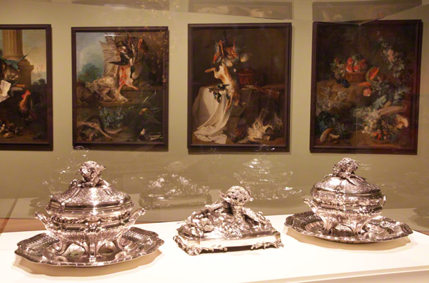View of <em>Paris: Life & Luxury</em>: silver tureens and centerpiece by François-Thomas Germain from the J. Paul Getty Museum's collection; culinary still lifes by Jean-Baptiste Oudry on loan from the Nationalmuseum, Stockholm, hang nearby.
