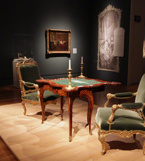 Inside the galleries of <em>Paris: Life & Luxury</em>: a gaming table, chairs, and candlesticks
