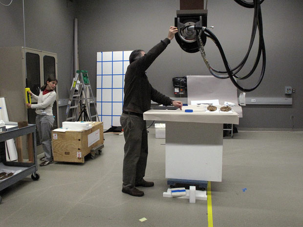 X-raying objects at the Getty Villa: Jeff Maish measures the distance between the table and the machine, while student Tessa de Alarcon adjusts the equipment to the desired height