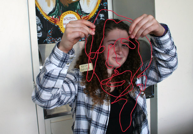 A student and her self-portrait sculpture in coated wire made from Mark Bradford's RE-RE-Process activity in Open Studio