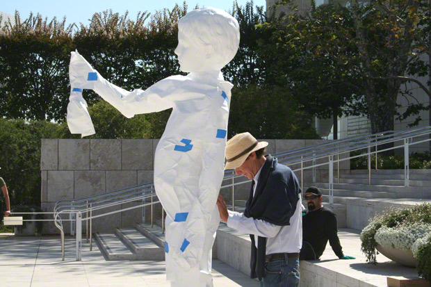 Artist Charles Ray checks the angle of Boy with Frog during its installation at the Getty Center