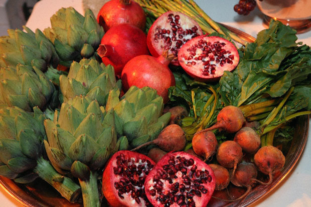 Artichokes and pomegranates on a serving table for At the Roman Table at the Getty Villa