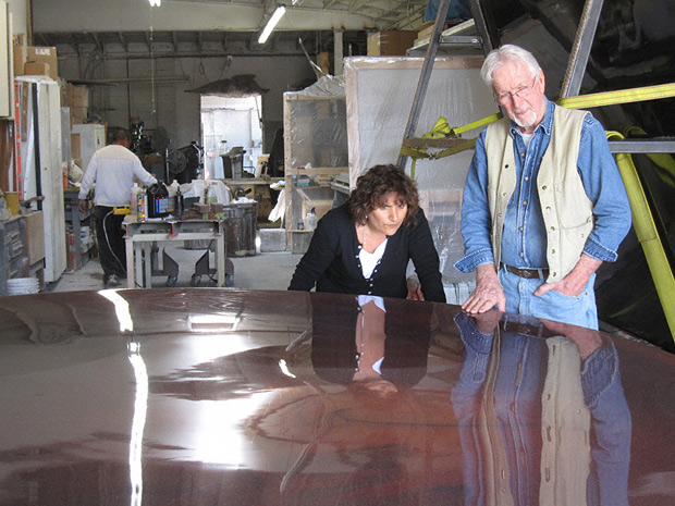 Jack Brogan, fabricator, and Rani Singh of the Getty Research Institute inspect De Wain Valentine's Red Concave Circle in Brogan's studio in Inglewood, California, June 17, 2011