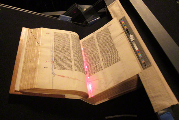 The Abbey Bible in the cradle for photography, showing the laser beam used to ensure that the page is parallel to the camera lens