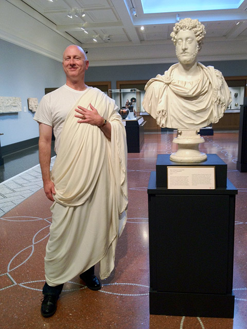 Guy Wheatley modeling a toga in the galleries of the Getty Villa