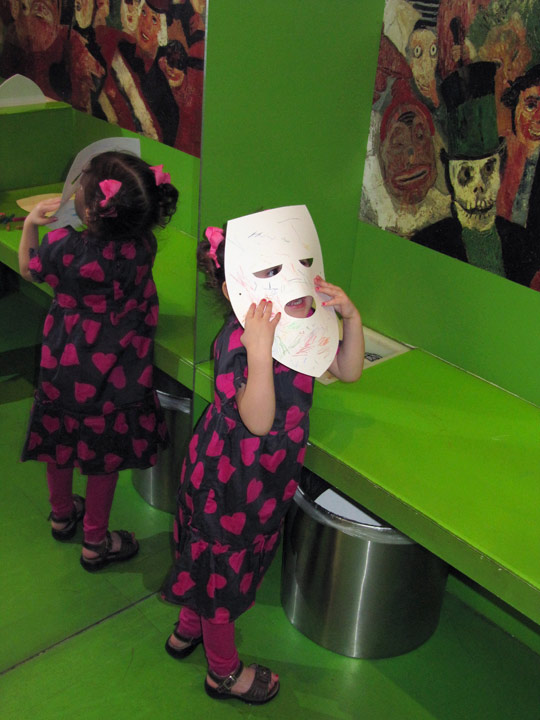 A girl shows off a mask she decorated in the Getty Center's Family Room