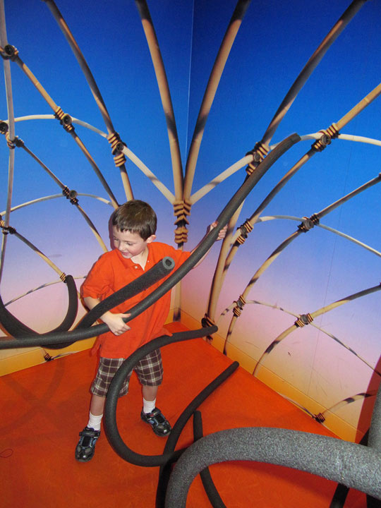 A boy plays in the tube sculpture in the Getty Center's Family Room