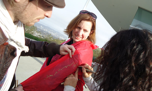 Lita Albuquerque signs Amy Hood's jumpsuit after the performance of Spine of the Earth 2012