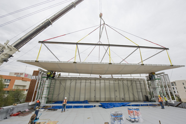 The canopy to protect the mural America Tropical, weighing 73,000 pounds and boasting an impressive 90-foot span, was lifted aloft by a construction crane and set into place.