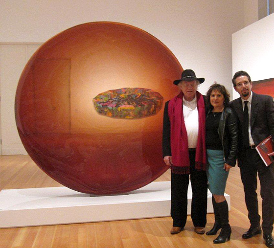 Artist De Wain Valentine with Rani Singh and Andrew Perchuk in front of his monumental polyester resin sculpture Red Concave Circle