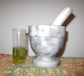 Ingredients for making perfume: olive oil and a mortar and pestle