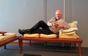 Getty Villa docent Don Petersen reclines on his left side, elbow raised on a stack of pillows, with his right knee bent. He holds a skyphos, a common stemless drinking cup.