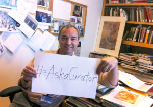 Julian Brooks of the Getty Museum's Department of Drawings with an #askthecurator sign