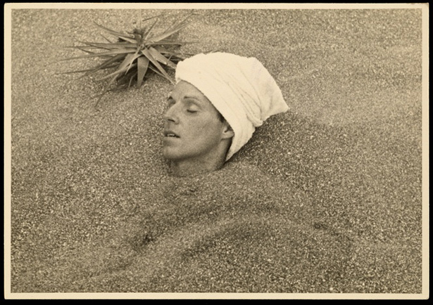 Photograph of Csar Moro buried up to his head in sand