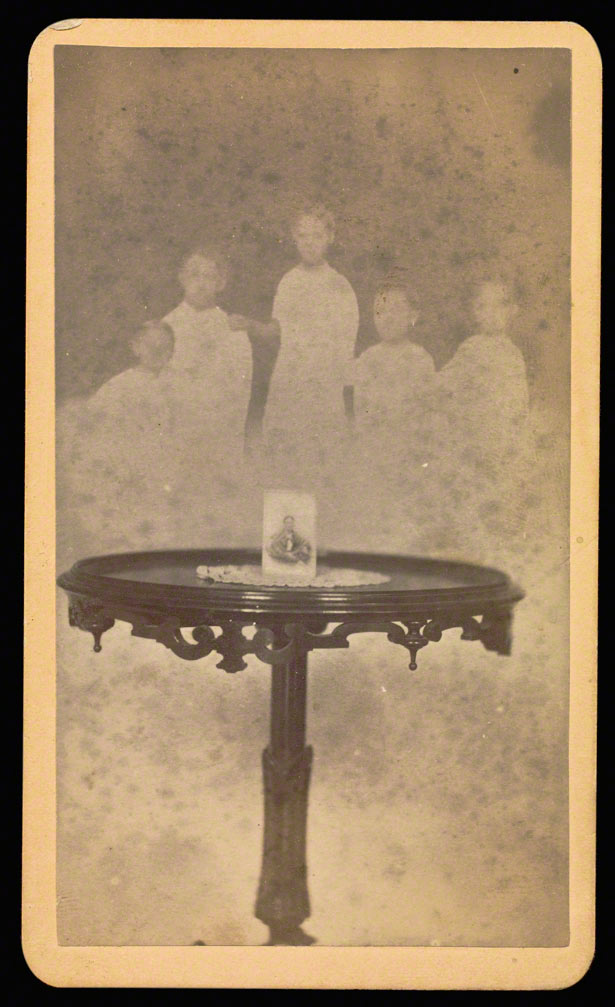 Five spirits in background with a photograph at center of table with a doily / William H. Mumler