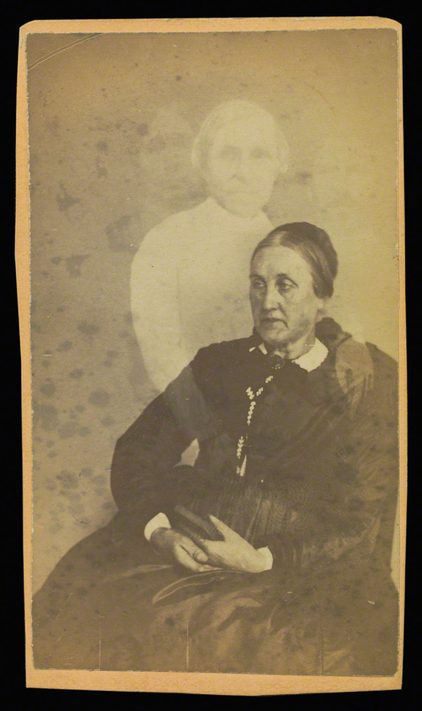 Unidentified elderly woman seated, three spirits in the background / William H. Mumler
