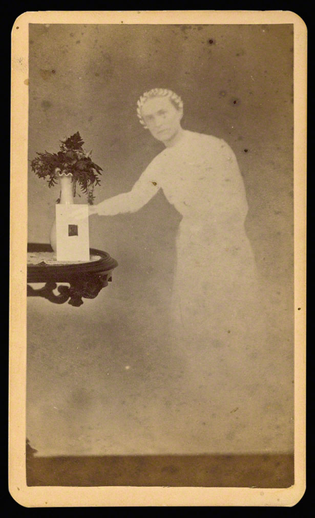 "Female ""spirit"" standing next to a table with a photograph propped against a vase with flowers / William H. Mumler"