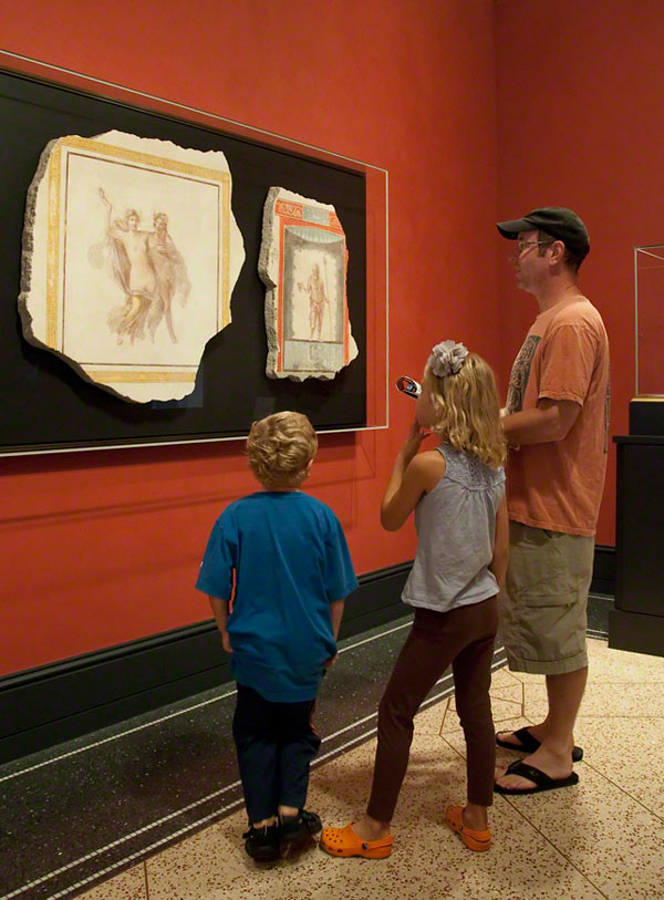 A family visiting the Getty Villa looks at Roman frescoes from Herculaneum