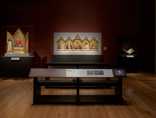 Installation view of Florence at the Dawn of the Renaissance showing pews and iPads