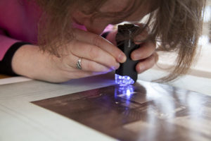 Miriam looks through her handy magnifying glass and light to try to determine the photographic process of this image.
