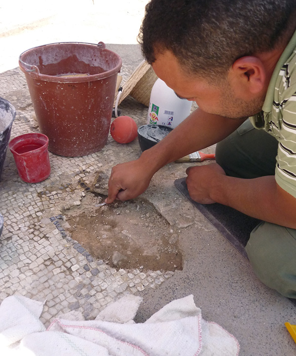 MOSAIKON conservation trainee conserving a mosaic in Bulla Regia, Tunisia