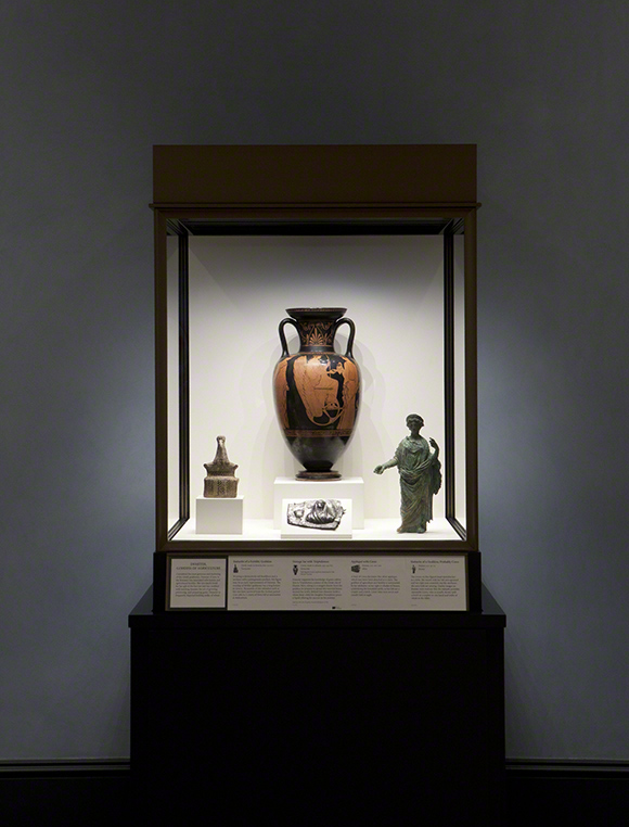 Display case at the Getty Villa featuring Red-Figure Neck-Amphora with Triptolemos Attended by Demeter and Persephone
