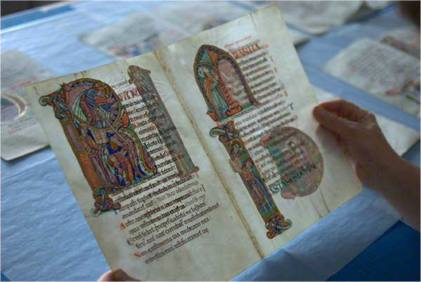 Conservator's hands holding the parchment of the St. Albans Psalter