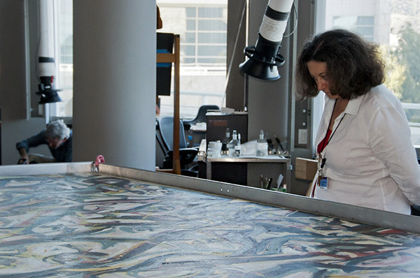 Yvonne Szafran in the Getty Museum's paintings conservation studio with Jackson Pollock's Mural.